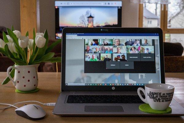 Laptop mit Zoom-Meeting und Kirche