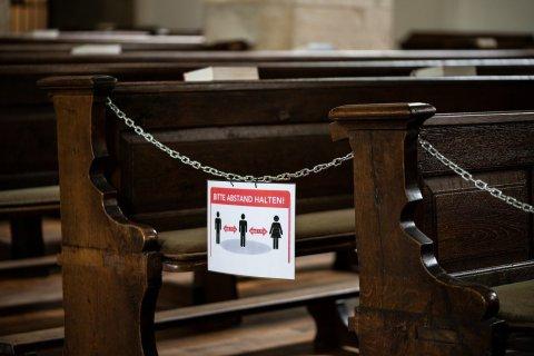 Kirchenbänke mit Hinweis zum Abstand halten